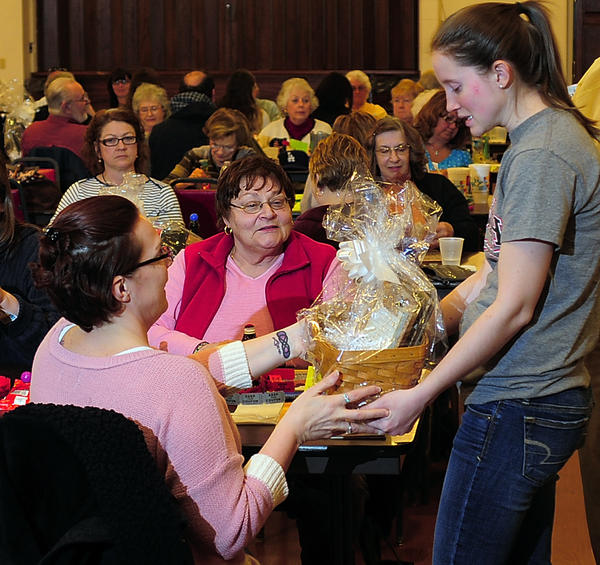 Hannah Bradley, right, delivers a vanity basket to bingo winner Jean Lauman on Sunday while Lauman's friend Dolores Vidoni, center, watches at a Longaberger basket, Vera Bradley and money bingo event Sunday at the Hagerstown Elks Lodge. All funds raised will benefit the University System of Maryland at Hagerstown Scholarship Fund, a fund of the University System of Maryland Foundation Inc. Bradley is president of the USMH student council.