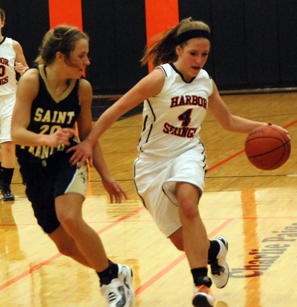 Harbor Springs junior guard Maddy Savard (right) pushes the ball up court as Traverse City St. Francis' Lauren Buckel defends during Friday's Lake Michigan Conference contest at the Harbor Springs High School gym.