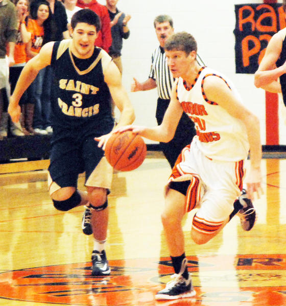 Harbor Springs senior forward Trevor Rohrer (right) pushes the ball up court as T.C St. Francis Kody Kleinrichert defends during Friday's Lake Michigan Conference at the Harbor Springs High School gym.