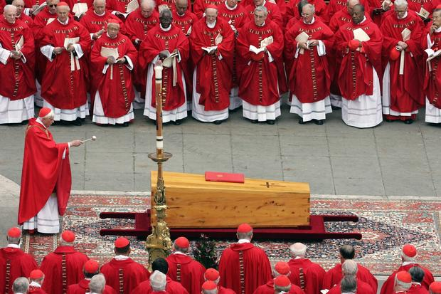 German Cardinal Joseph Ratzinger, who went on to take the papal name Benedict XVI, blesses the coffin of Pope John Paul II during his funeral Mass in St Peter's Square on April 8, 2005.
