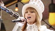 "Strutting the stage in her white tuxedo jacket, shorts and sparkling top hat, Taylor Swift opened Sunday's Grammy Awards with a live performance of her current hit, ""We Are Never Ever Getting Back Together."""