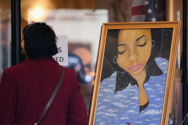 A mourner stands next to a painting of 15-year-old Hadiya Pendleton, placed at the entrance of the Calahan Funeral Home during her wake in Chicago.
