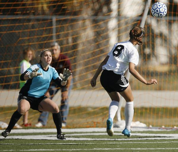American Heritage player Melanie Monteagudo (8) scores a goal past Ponte Vedra goalkeeper Kare Davidson (left) during the girls soccer 3A state championship game of American Heritage versus Ponte Vedra at Melbourne High School on Saturday, February 9, 2013. American Heritage won the game 3-0 to claim the state championship title.