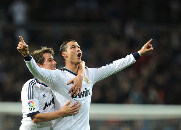 Real Madrid's Portuguese forward Cristiano Ronaldo (R) celebrates his goal with Real Madrid's Portuguese defender Fabio Coentrao during the Spanish league football match Real Madrid CF vs Sevilla FC at the Santiago Bernabeu stadium in Madrid on February 9, 2013.