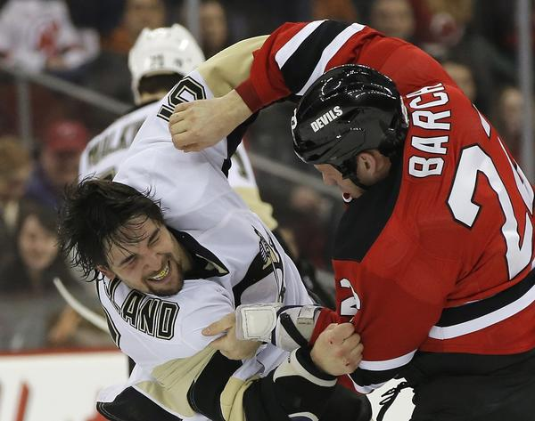 Pittsburgh Penguins defenseman Deryk Engelland and New Jersey Devils right wing Krys Barch (R) fight in the first period of their NHL hockey game in Newark, New Jersey, February 9, 2013.
