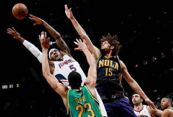 Josh Smith #5 of the Atlanta Hawks loses the ball against Anthony Davis #23 and Robin Lopez #15 of the New Orleans Hornets at Philips Arena on February 8, 2013 in Atlanta, Georgia.