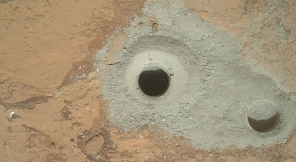 At the center of this image from NASA's Curiosity rover is the hole in a rock called 'John Klein' where the rover conducted its first sample drilling on Mars. The drilling took place on Feb. 8, 2013, or Sol 182.