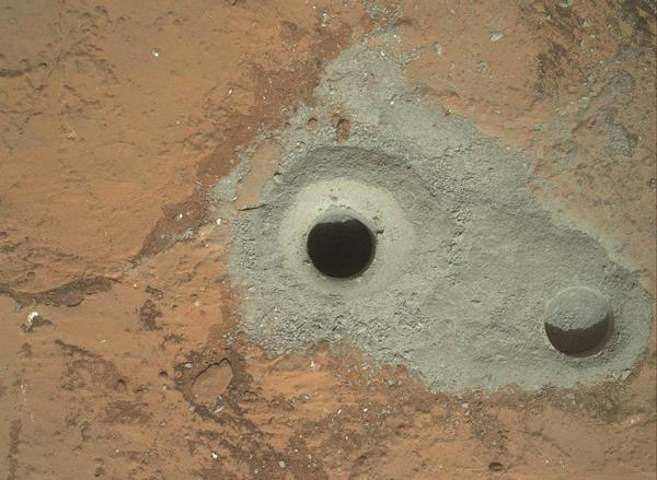 "Image taken by the Mars Hand Lens Imager shows the hole in a rock called ""John Klein"" where the rover conducted its first sample drilling on Mars. Several preparatory activities with the drill preceded this operation, including a test that produced the shallower hole on the right two days earlier."
