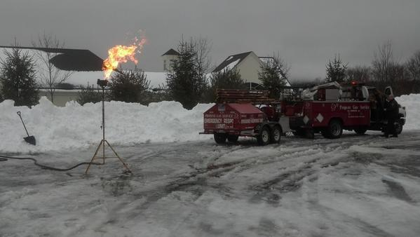 A fire crew safely bruns off propane gas after a  leak caused by a plow truck accident in Tolland Monday.
