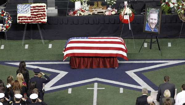 Taya Kyle and her children sit near the coffin of her slain husband former Navy SEAL Chris Kyle during a memorial service for the former sniper at Cowboys Stadium in Arlington, Texas, on Feb. 11. (Reuters)
