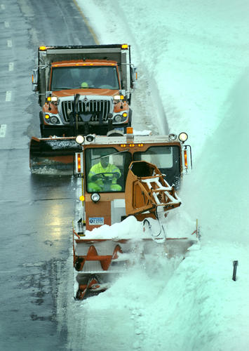 A giant Sno-Cat snowblower, which can clear an entire lane, works its way down I-384 West between exits 3 and 4 Monday morning in the rain as snow removal continues throughout the state.
