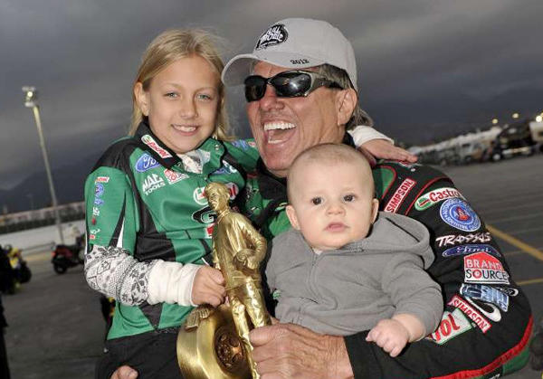 John Force celebrates earning his 134th career win at the NHRA Winternationals drag races with his grandchildren.