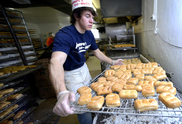 Tyler Puffenberger takes a load of fresh Krumpe's fastnachts to the rack after being iced on Monday in preparation for Fat Tuesday.