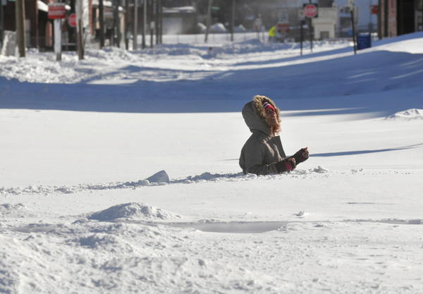 Evonna Hellandbrand crosses the unplowed intersection of Lawrence and Grand streets in Hartford on Saturday afternoon.