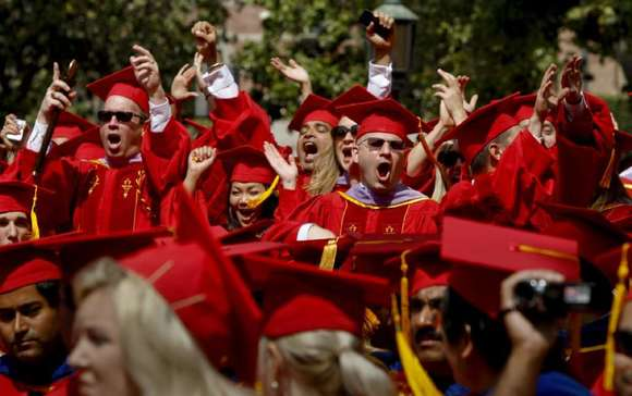 Some of the nearly 14,000 students receiving degrees are among the estimated 40,000 people filling Alumni Park at USC.