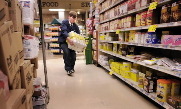 Chris Parsons of East Granby, assistant grocery manager at Geissler's IGA in Bloomfield, restocks the severely depleted shelves at the local grocery store Monday. Shipments of produce and other food items are arriving gradually for restocking shelves that were emptied out on Friday before the blizzard hit the state.