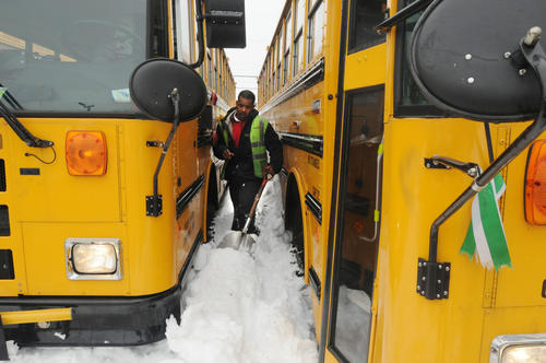 Emanuel Chaney, of Hartford, a bus driver for First Student, West Hartford, shovels out between two buses Monday afternoon in West Hartford as the school bus company, with locations in West Hartford, East Hartford and Bloomfield, prepares its fleet to take students to school.