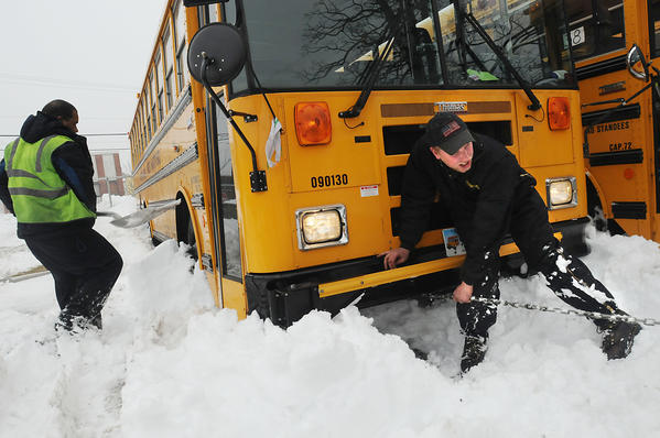 Emanuel Chaney, of Hartford, a bus driver for First Student, West Hartford, left, shovels out next to a bus Monday afternoon in West Hartford as mechanic Joel Lech, of Enfield, hooks up a chain to have the bus pulled out of its snowed-in slot as the school bus company, with locations in West Hartford, East Hartford and Bloomfield, prepares its fleet to take students to school.