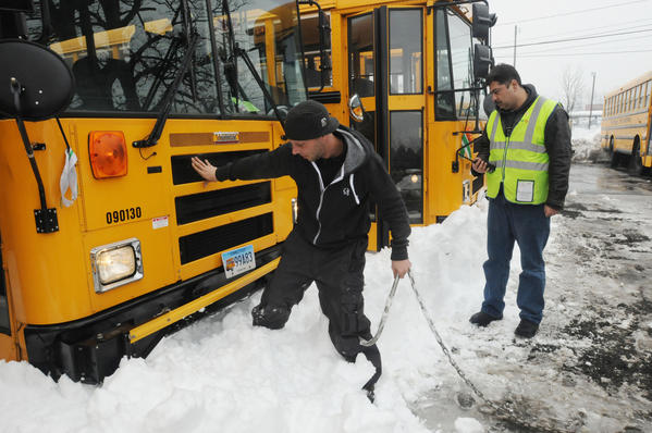 David Palla of East Hartford, who works for Corr Services and was plowing the First Student Parking lot in West Hartford Monday kicks snow aside in order to attach a chain to pull a bus out of the snow. Muhammad Minhas, of West Haven, location manager for First Student, at right, looks on.