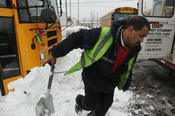 Emanuel Chaney, of Hartford, a bus driver for First Student dashes out of the way as a bus is towed by a chain out of a snow bank in the company lot in West Hartford Monday. He had been helping to clear snow out from under the buses.