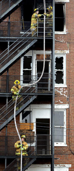 Firefighters hoist a hose at the rear of the five-story building Friday at 21 West Antietam Street where a fire had erupted Thursday evening. Demolition work continues on the building.