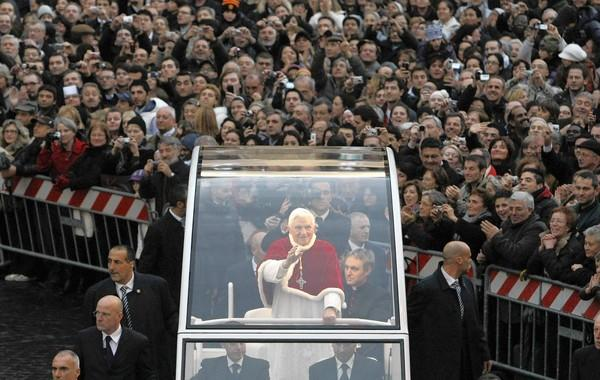 Pope Benedict XVI waves from his popemobile in Rome. During his papacy, Benedict spoke out against the sexual abuse of children by Roman Catholic priests, but critics believe he did not do enough.