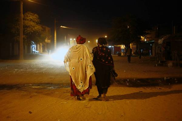 Women walk through Timbuktu, Mali, on Feb. 2, moments after the street lights came back on for the first time in months. The town's occupation by Islamic extremists made life difficult for residents until French and Malian forces drove the militants out.