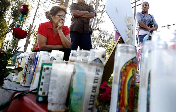 Passersby stop at the memorial for a mother, daughter and cousin who were struck and killed by a suspected drunk driver Saturday night while crossing a street in Anaheim.