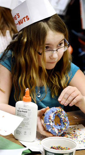 Old Forge Elementary third-grader Charlotte Harshman decorates her papier mach doughnut with colored rice and beads for the class's Fat Tuesday display.