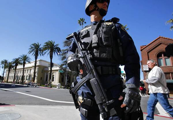 Heavily armed law enforcement officers stand guard at a news conference after the Riverside County district attorney filed criminal charges against Christopher Jordan Dorner.