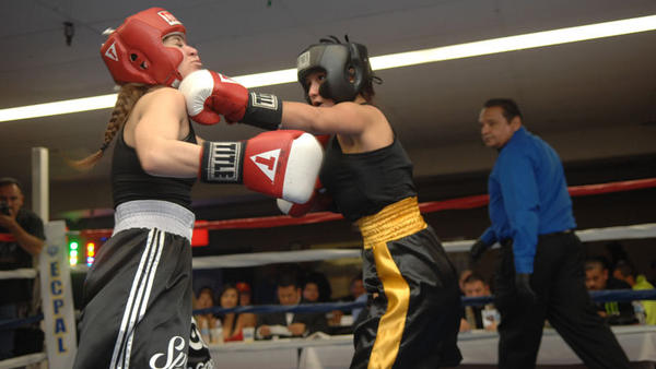 Tania Solis (right) of Solo Boxing Club delivers a jab to the chin of Ivonne Zamudio of Sparta Boxing on Saturday during the inaugural Queens of Fury all-female charity boxing tournament at the El Centro PAL Ryerson Youth Center.