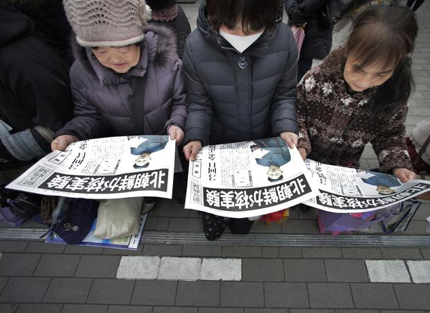 Women in Tokyo read copies of a delivered extra edition of a Japanese newspaper reporting North Korea's nuclear test.