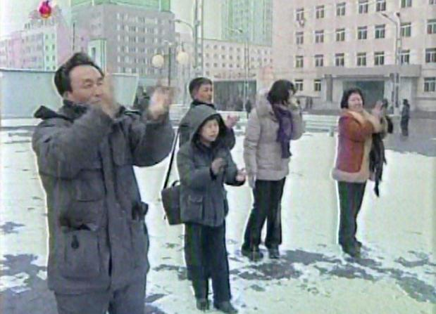 North Koreans celebrate as they watch an announcer reading a statement on the country's nuclear test on a large television screen in front of Pyongyang's railway station.