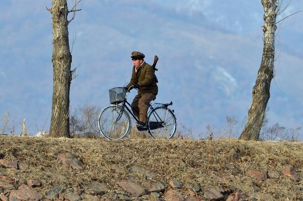 A North Korean soldier rides a bike beside a crossing of the Yalu River near the North Korean town of Sinuiju after the country conducted its third nuclear test.