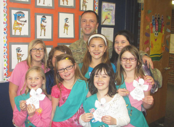 "Girl Scout Brownies from Troop 3569 at Petoskey's Sheridan Elementary gather with U.S. Army Spc. Daniel Glezman (back) during his recent visit to the school. As part of the ""Operation Downtime"" initiative, local nonprofit organization Angel Ambassadors sought items from the community to be sent to military battalions stationed in Afghanistan, with the goal of providing troops with some enjoyment during their down time. Contributions from the Brownie troop, Gaylord High School, Harbor Springs IGA, Dunham's Sports and private donors allowed Angel Ambassadors to send two large packages of food and recreational equipment to military members. Glezman, of Petoskey, recently surprised the Brownies at school to express his appreciation. Spc. Brandon Kargol of Petoskey, another recipient of the contributions, sent a letter and picture to the girls."