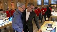 Apple CEO Tim Cook, left, visits the Apple Store in New York's Grand Central Station.
