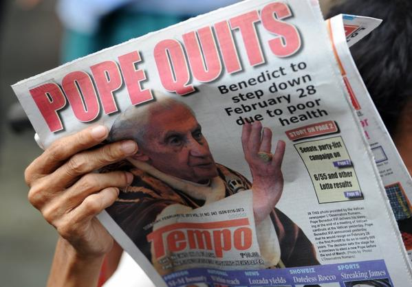 A vendor reads a newspaper featuring the story of the resignation of Pope Benedict XVI near a church in Manila.