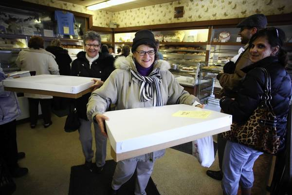 Eileen Lenten, front, and friend Harriet Stock both of Berwyn carry out two boxes containing 68 paczkis for their co-workers.