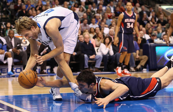Dirk Nowitzki #41 of the Dallas Mavericks tries to grab a loose ball against Zaza Pachulia #27 of the Atlanta Hawks at American Airlines Center on February 11, 2013 in Dallas, Texas.