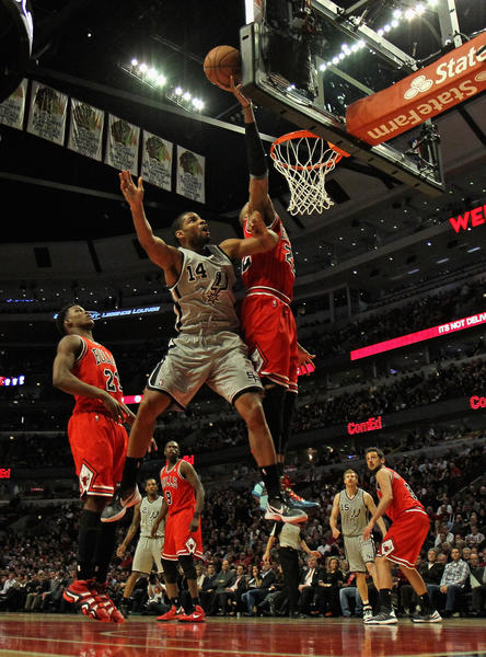 Taj Gibson #22 of the Chicago Bulls blocks a shot by Gary Neal #14 of the San Antonio Spurs at the United Center on February 11, 2013 in Chicago, Illinois. The Spurs defeated the Bulls 103-89.