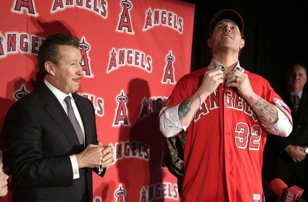 New Angels outfielder Josh Hamilton, shown with owner Arte Moreno in December, arrived at camp some 20 to 30 pounds lighter than his usual spring weight with the Texas Rangers.