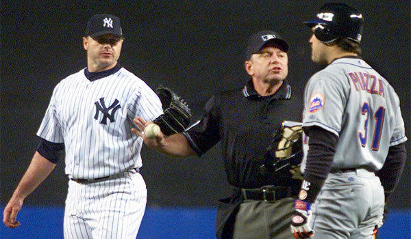 Home plate umpire Charlie Reliford steps between New York Mets' Mike Piazza (31) and New York Yankees pitcher Roger Clemens after Clemens threw a part of Piazza's bat back at him during Game 2 of the 2000 World Series.