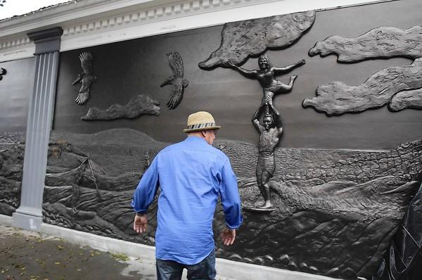 Sculpture artist Randy Morgan looks over his Waterman's Wall mural after the unveiling in November.