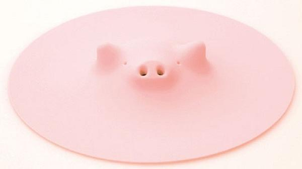 Silicone Piggy Steamer pot cover from the 141-year-old Japanese company Marna. When placed over a pot, steam comes out the piggy's snout.