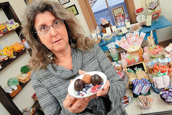 Susan Benjamin, owner of Cool Confectionaries in Harpers Ferry, W.Va., holds a plate of chocolate truffles and sugar-coated flower petals. She names these type of botanical items as aphrodisiacs.