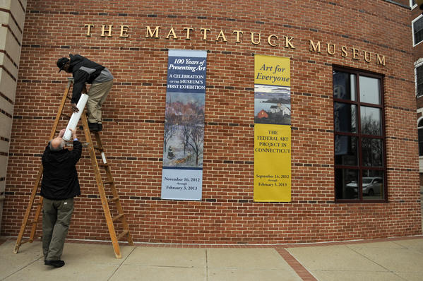 Two men take down banners outside the Mattatuck Museum in Waterbury before hanging new ones announcing new exhibits. The museum is housed in a historic former Masons Lodge near the Waterbury Green.