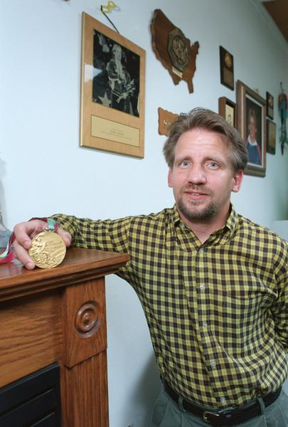 Bobby Weaver, 1984 Olympic Gold Medalist in wrestling, holds the gold medal he won at the summer Olympics in Los Angeles in the living room of his Easton.