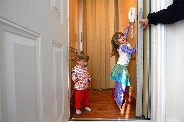 Families juggling children, pets and groceries are among those who are adding home elevators. Above, Aden Enzer, 5, and her sister Bennett, 2, use the elevator at their family's Hancock Park home.