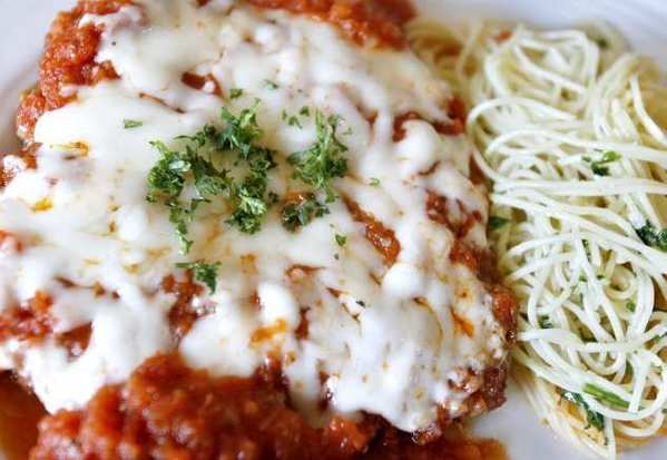 Trattoria Mediterranean's Pollo Alla Parmigiana features chicken breast lightly breaded, pan-seared, and oven-baked, topped with tomato sauce and shredded mozzarella cheese and served with cappellini, garlic, olive oil and Parmesan cheese.