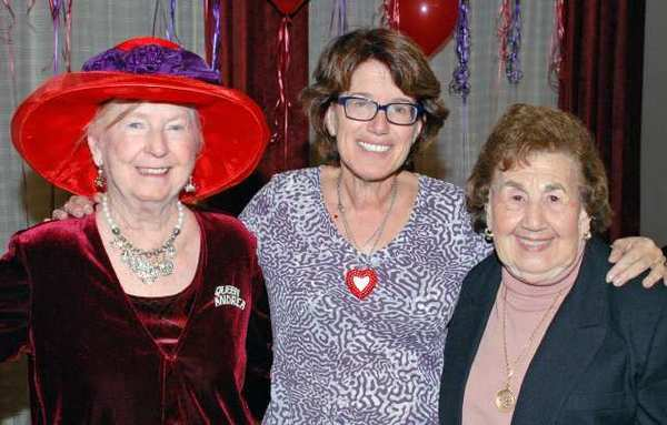 Gayle Migden, flanked by her mother, Sadie Migden, right, and Queen Andrea Allen, was the guest of honor as the local Red Hatters celebrated their 10th anniversary.